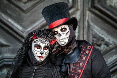 European destinations to spend Halloween | Sugar skull masked dressed as married couple at Venice carnival in Italy