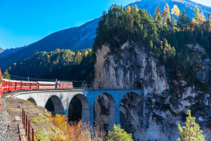 Bernina Express scenic train entering tunnel on the Albula Railway in Switzerland