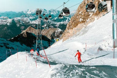TOP 5 Europe Winter Destinations | Skiing people and moving cable cars above them in Kitzsteinhorn, Austria