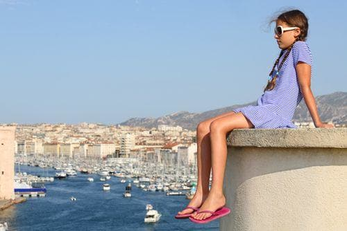 2 weeks in France for families | Girl with views of old port in Marseille France