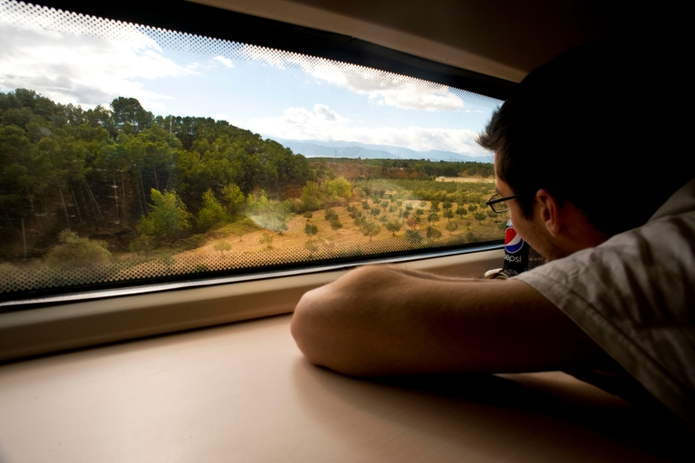 Man looking at scenic landscape from AVE train window, Almeria-Granada, Spain