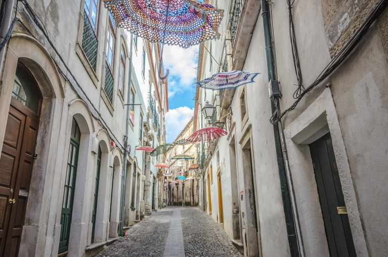 Umbrellas hanging in a narrow street in Coimbra