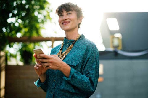 Everything about Eurail | Smiling woman with a mobile