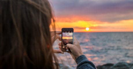 Why Eurail is your greenest choice | Female taking a photo of sunset with mobile at Vang, Hasle in Denmark