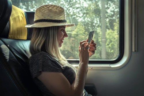 Everything about Eurail | Woman sittiing in the train and looking into the mobile